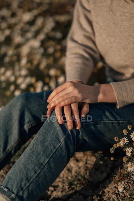 Невпізнаваний подорожній у повсякденному одязі сидить сам на квітучому лузі на розмитому полі і відпочиває в сільській місцевості навесні. — стокове фото