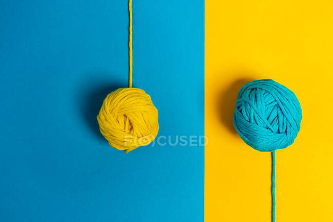 From above of small woolen thread balls representing lollies on sticks on blue and yellow background — Stock Photo