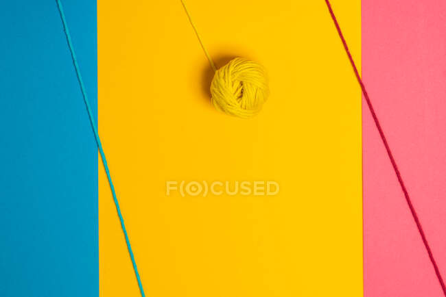 From above of small woolen thread balls representing lollies on sticks on blue, yellow and pink background — Stock Photo