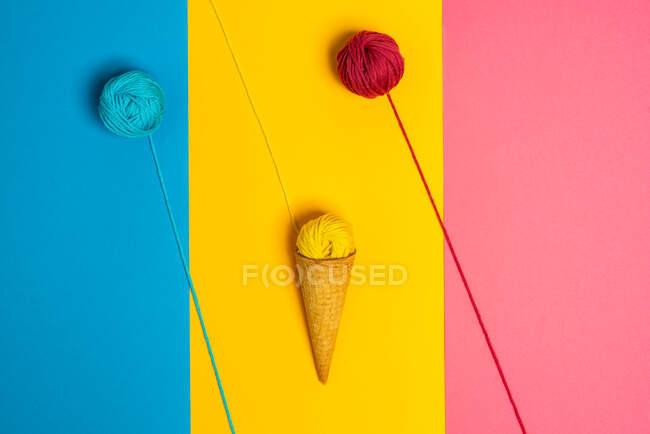 Bolas de hilo de lana de colores en cono crujiente natural que representa varios gelato sobre fondo de tres colores - foto de stock