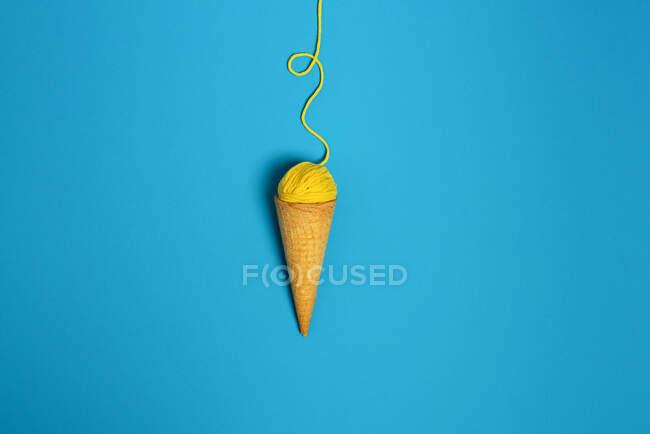 Bola de hilo de lana colorida en cono crujiente natural que representa gelato sobre fondo azul - foto de stock