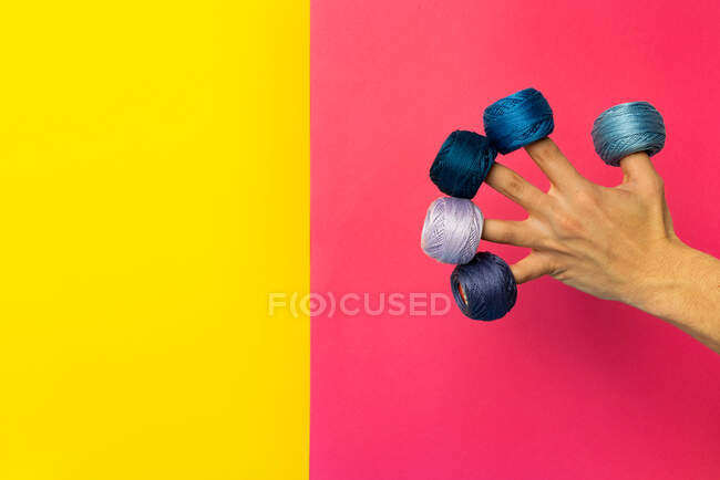 Crop anonymous female artisan showing collection of yarn balls with thin threads on pink and yellow background — Stock Photo