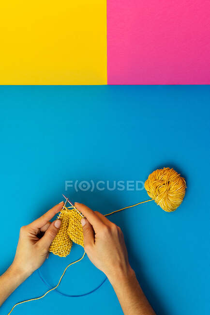 Top view of crop anonymous female artisan knitting with metal needles using yarn ball on three color background — Stock Photo