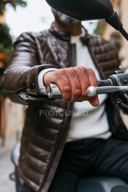 From below cropped unrecognizable male biker driving contemporary motorbike while looking forward in town — Stock Photo