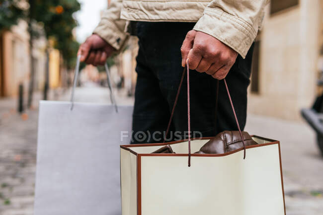 Cropped unrecognizable man with shopping bags strolling on urban walkway — Stock Photo