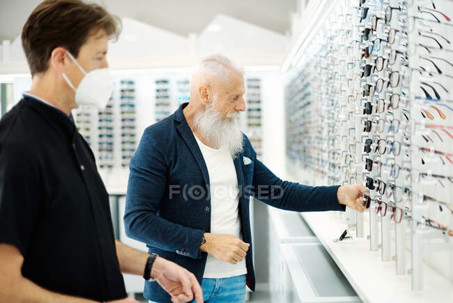 Side view of optician in mask and senior male choosing eyeglasses and sunglasses in optical store — Stock Photo
