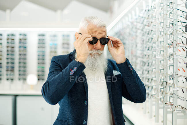 Senior male in trendy outfit trying on stylish sunglasses in modern optical store — Stock Photo