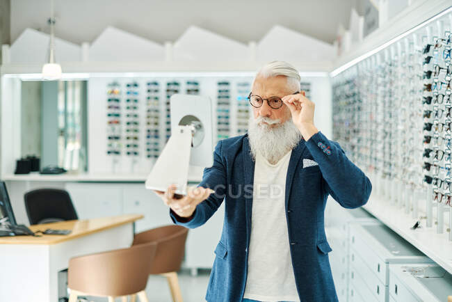 Stylish senior male looking in mirror while trying on and choosing eyeglasses in modern optical shop — Stock Photo
