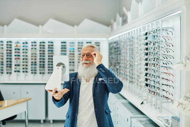 Content stylish senior male looking in mirror while trying on and choosing eyeglasses in modern optical shop — Stock Photo