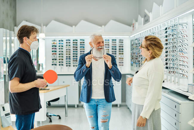 Optician with mirror helping content elderly male trying on eyeglasses in optical store — Stock Photo