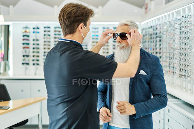 Side view of professional optician in mask helping senior male putting sunglasses while working in optical store — Stock Photo