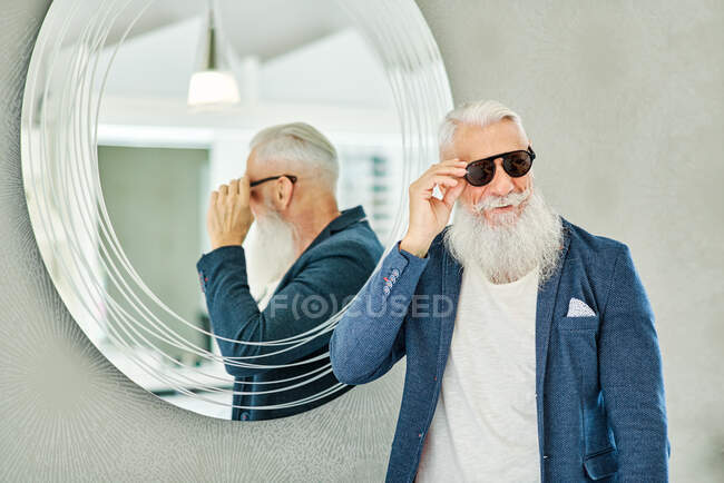 Cheerful stylish senior male standing near mirror in optical store and trying on trendy sunglasses — Stock Photo
