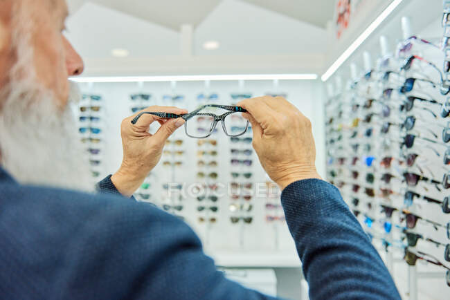 Serious elderly bearded male in trendy outfit standing with modern stylish glasses in optical shop — Stock Photo