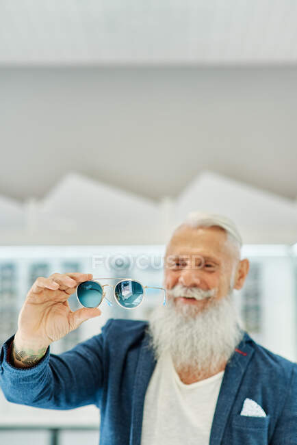 Happy elderly bearded male in trendy outfit standing with modern stylish sunglasses in optical shop — Stock Photo