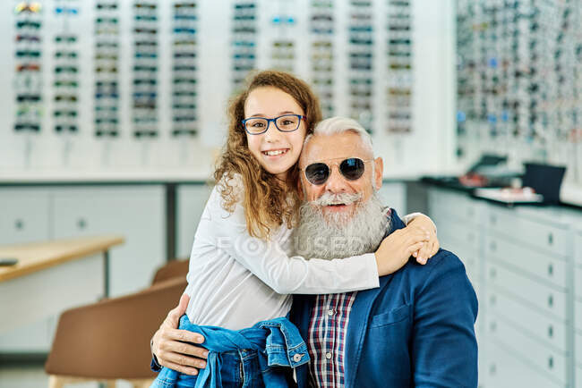Smiling stylish grandpa and cute girl wearing trendy glasses while embracing in modern optical store and looking at camera — Stock Photo