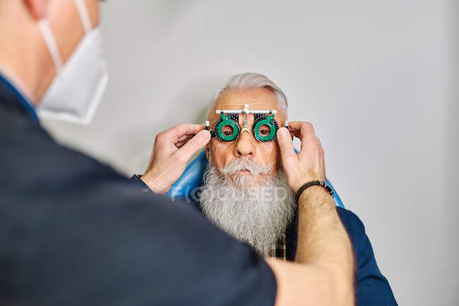 Crop ophthalmologist putting on eye test glasses on face of elderly patient for vision diagnostics in clinic — Stock Photo
