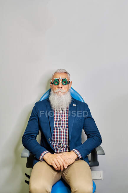 Bearded elderly male in eye test glasses sitting in modern clinic before vision examination and looking at camera — Stock Photo