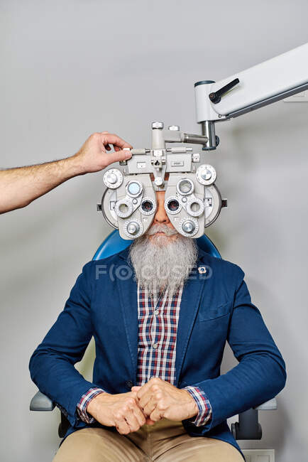 Augenoptiker mit Phoropter bei Sehtest älterer männlicher Patient in Klinik nicht wiederzuerkennen — Stockfoto