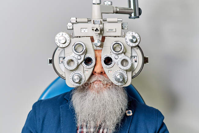 Senior male with phoropter during eye examination — Stock Photo