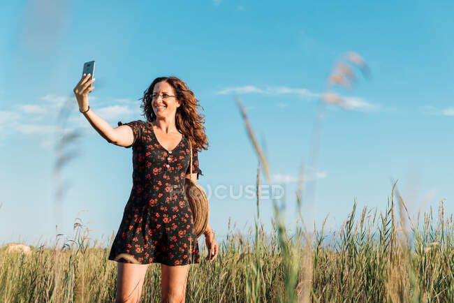 Delighted female in summer dress standing in field and taking self portrait on smartphone at sunset — Stock Photo