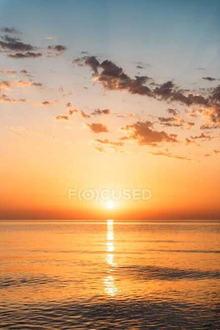Vue panoramique du coucher de soleil orange vif sur l'eau de mer calme le soir — Photo de stock