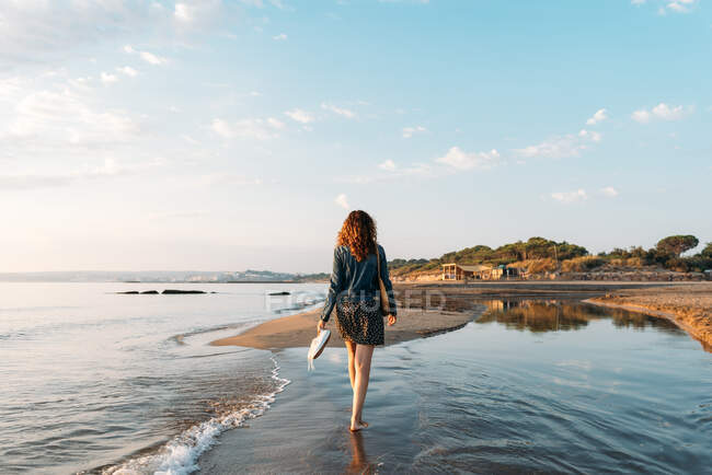Back view of female walking in water of sea and admiring spectacular view of colorful sundown sky in summer — Stock Photo