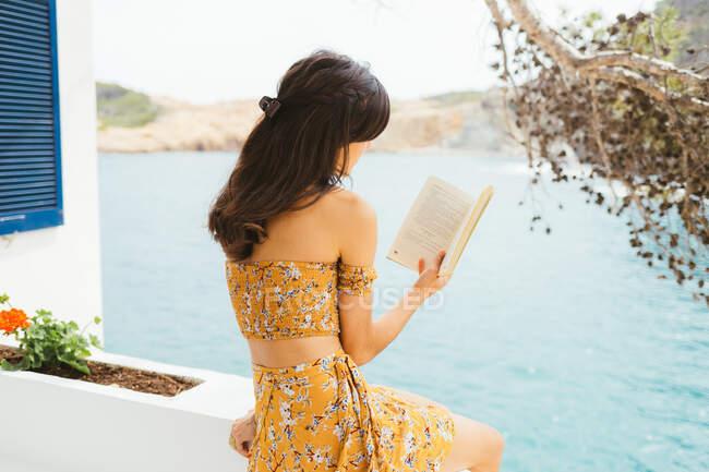 Вид сбоку романтичной молодой женщины в летнем наряде, сидящей на террасе у воды озера и читающей интересный роман в книге, проводя лето за городом — стоковое фото