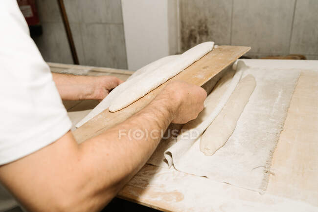 Crop anonymous male baker putting raw bread dough on tray on wooden surface at work — Stock Photo
