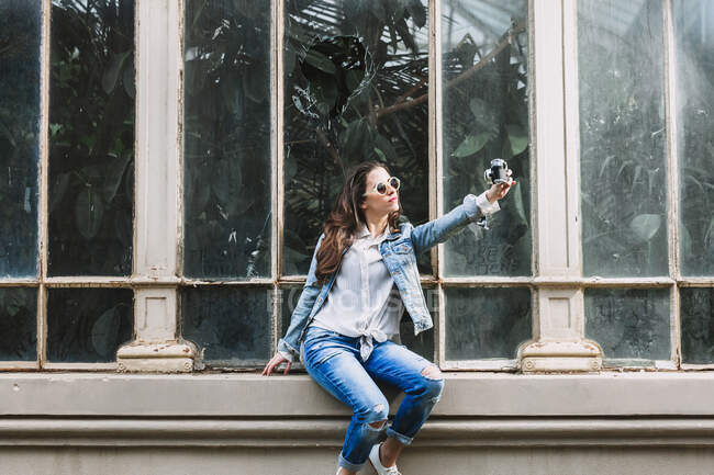 Mujer fresca en gafas de sol y ropa de mezclilla tomando autorretrato en la cámara de fotos mientras se sienta contra la ventana de naranjería en la ciudad - foto de stock