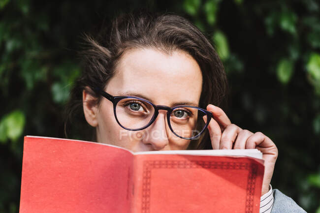 Content female student in glasses and with notepad standing in park and looking at camera — Stock Photo