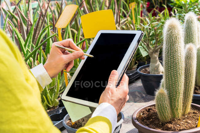 Жінки - садівники використовують сучасні планшети, рахуючи рослини і працюючи в садовому центрі. — стокове фото