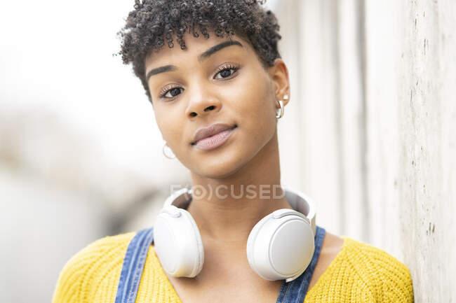Femme afro-américaine souriante rêveuse dans un casque sans fil tout en se tenant dans la rue en regardant la caméra — Photo de stock