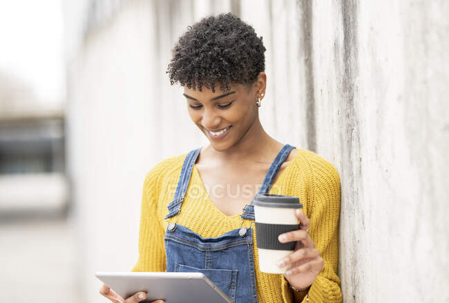Glad black female standing on street with coffee to go in paper cup and watching video on tablet while entertaining at weekend in city — Stock Photo