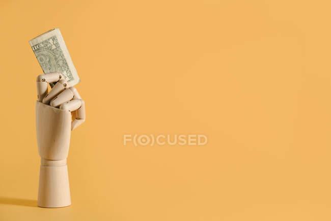 Billets en dollars en bois placés à la main sur fond orange en studio montrant le concept financier — Photo de stock