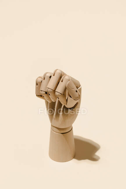 High angle of wooden hand showing clenched fist on beige background in studio — Stock Photo