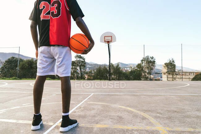 Cropped back view of unrecognizable African American male streetball player in uniform standing with ball on basketball court — Stock Photo