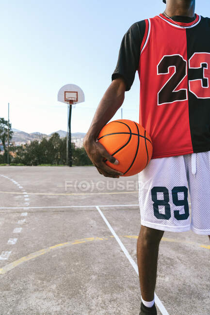 Cropped unrecognizable African American male streetball player in uniform standing with ball on basketball court — Stock Photo