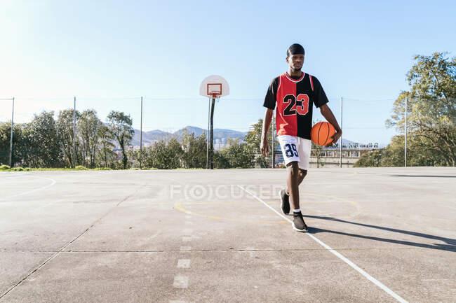 Серьезный афроамериканец в форме ходит с мячом на баскетбольной площадке и смотрит в камеру — стоковое фото