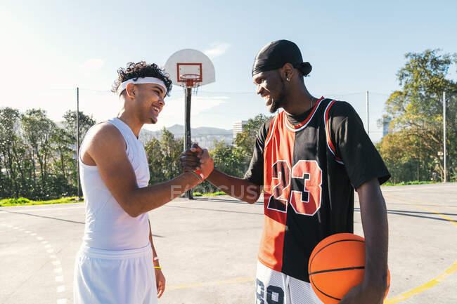 Вид сбоку на афроамериканских игроков в стритбол, пожимающих руку, стоя на баскетбольной площадке и глядя друг на друга — стоковое фото
