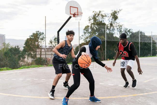 Мультиэтнические друзья летом играют в уличный баскетбол на спортивной площадке — стоковое фото