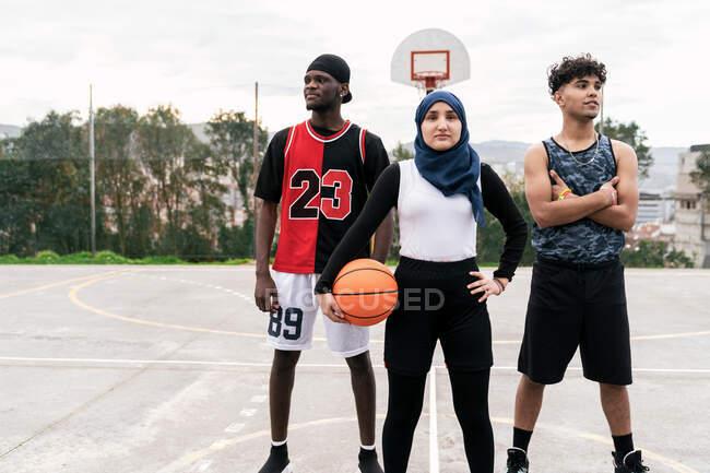 Уверенная многонациональная команда по стритболу с мячом, стоящая на баскетбольной площадке в городе — стоковое фото