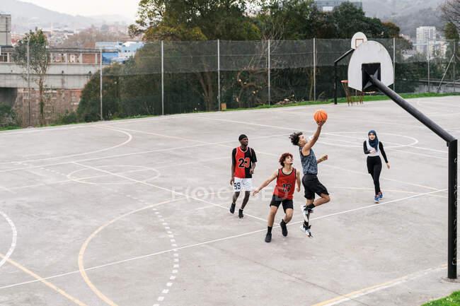 Высокий угол многонациональных друзей, играющих в уличный баскетбол на спортивной площадке летом — стоковое фото