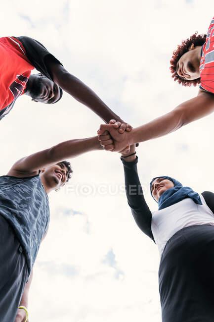 D'en bas de l'équipe multiraciale de joueurs de streetball empilant les mains ensemble avant le match de basket-ball — Photo de stock