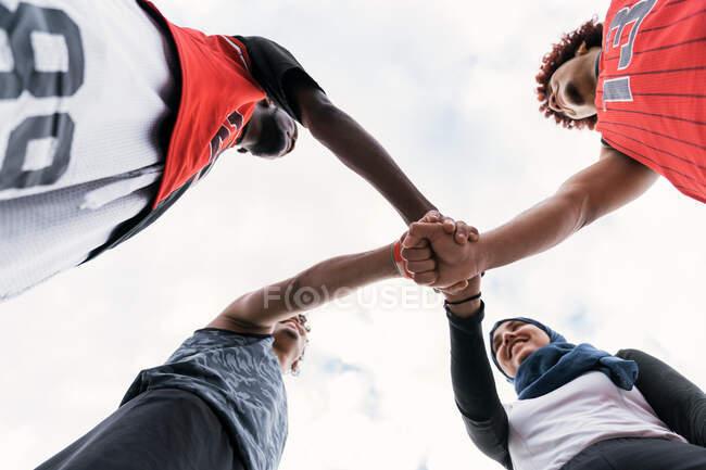 Desde abajo del equipo multirracial de jugadores de streetball apilando manos juntos antes del partido de baloncesto - foto de stock