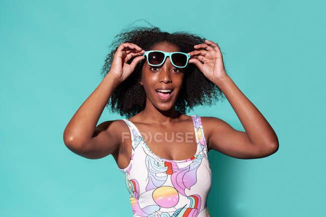 Atractiva mujer afroamericana feliz vistiendo traje de baño de moda y poniéndose gafas de sol mientras está de pie sobre fondo azul y mirando a la cámara - foto de stock