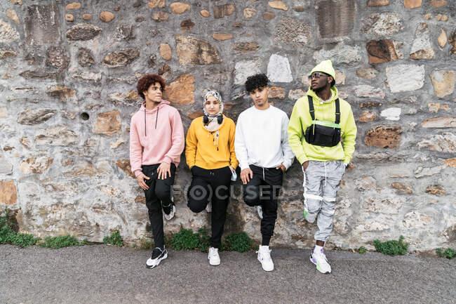 Groupe d'amis cool multiethnique dans des tenues de style de rue debout près du mur de pierre en ville — Photo de stock