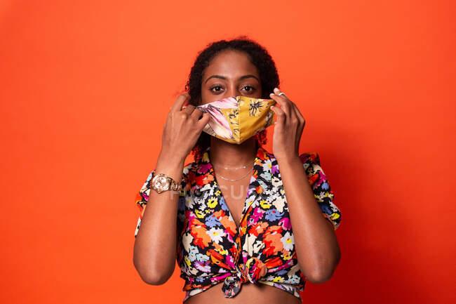 Jovem fêmea afro-americana atraente em top colorido colocando máscara facial de pano e olhando para a câmera contra o fundo vermelho — Fotografia de Stock