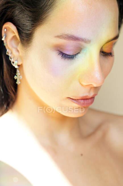 Young tender female in earrings with makeup looking down on sunny day — Stock Photo
