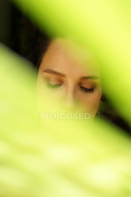 Young lonely gentle female with eyes closed standing behind colorful green plant leaf — Stock Photo