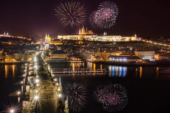 Amazing view of bright fireworks exploding in dark night sky over city with illuminated buildings — Stock Photo